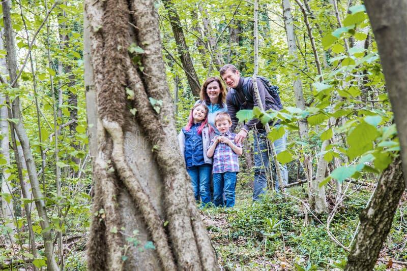 St?ende av den lyckliga familjen i skogen arkivfoto