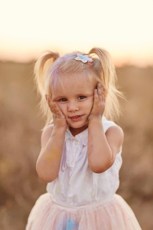 St?ende av den lyckliga flickan suddig med kul?rt pulver Liten flicka med tv? svansar royaltyfria bilder
