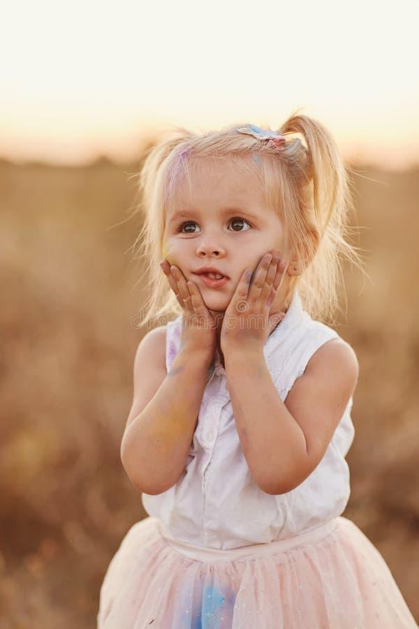 St?ende av den lyckliga flickan suddig med kul?rt pulver Liten flicka med tv? svansar arkivbild