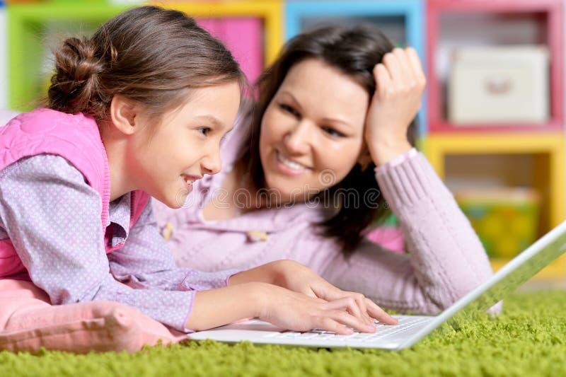 St?ende av den lyckliga modern och dottern som tillsammans anv?nder b?rbara datorn royaltyfria bilder