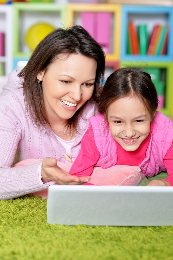 St?ende av den lyckliga modern och dottern som tillsammans anv?nder b?rbara datorn arkivfoton