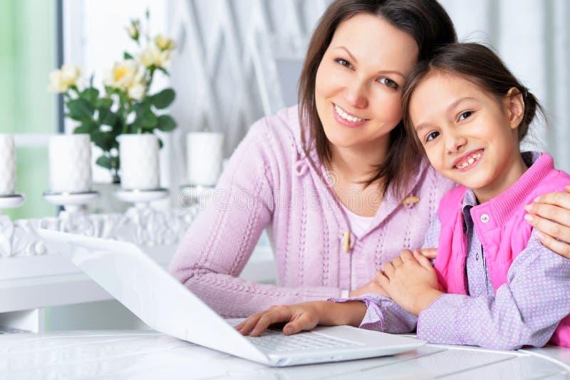 St?ende av den lyckliga modern och dottern som tillsammans anv?nder b?rbara datorn arkivfoto
