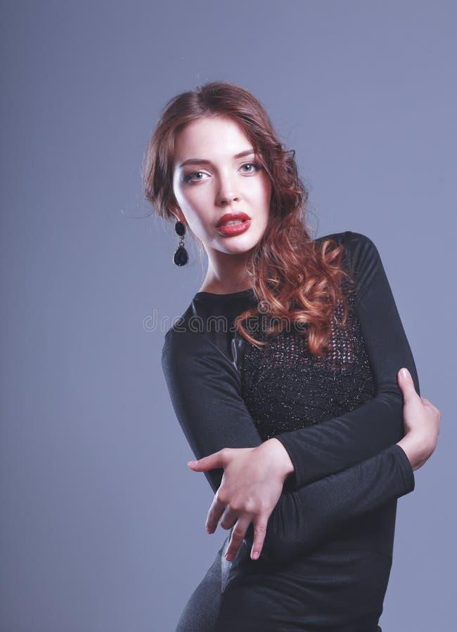 St?ende av den lyckliga unga kvinnan i svart kl?nning p? gr? bakgrund royaltyfria foton