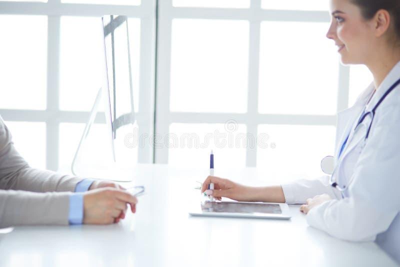 St?ende av den mitt ?ldrades kvinnliga doktorn som anv?nder den digitala minnestavlan, medan sitta p? examenrum och arbete fotografering för bildbyråer