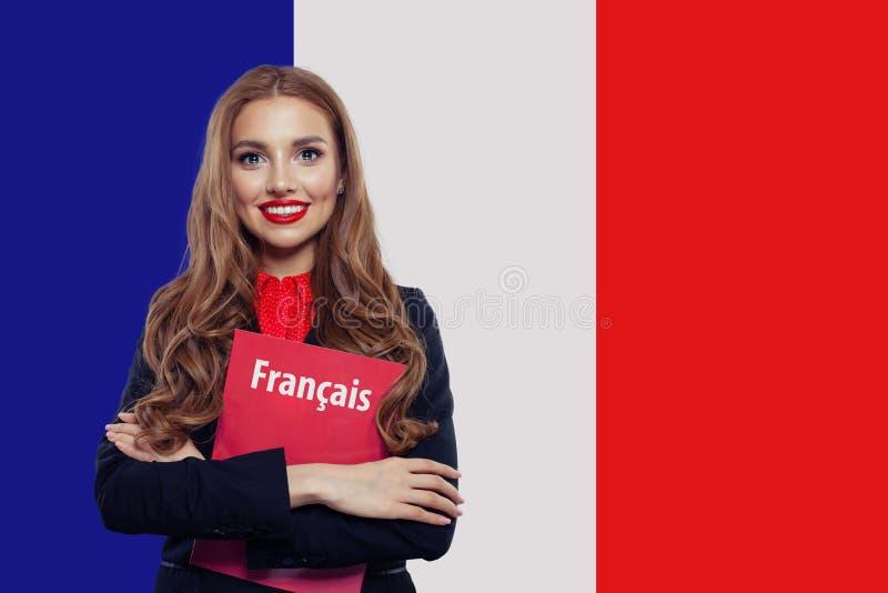 St?ende av den n?tta unga le kvinnan med boken p? den franska flaggabakgrunden Lopp i Frankrike och studie i franskt språk royaltyfria bilder