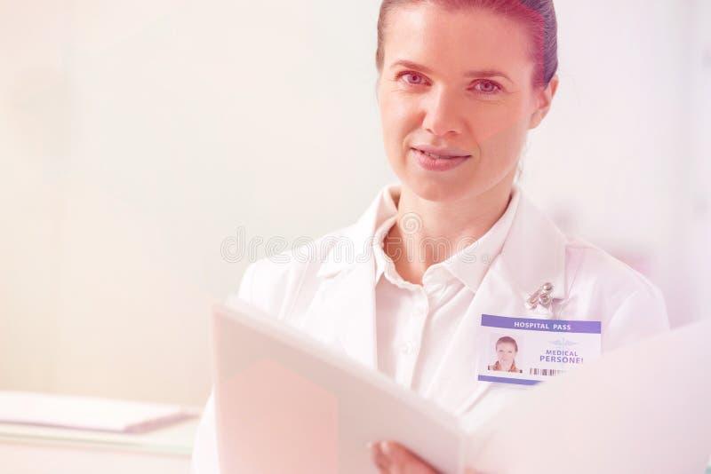 St?ende av den s?kra kvinnliga doktorsinnehavmappen p? kliniken royaltyfri fotografi