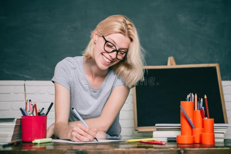 St?ende av den s?kra unga Caucasian l?rarinnan E Examen i h?gskola kvinnlig arkivfoto
