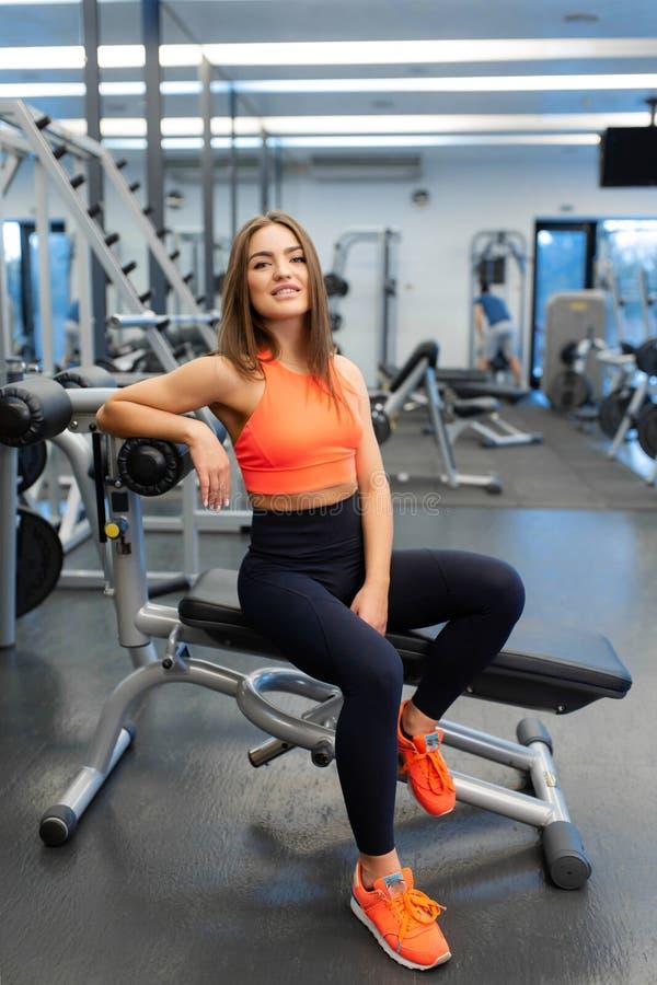 St?ende av den slanka stiliga unga kvinnan att koppla av i idrottshall efter h?rd utbildning arkivbilder