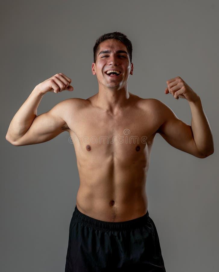 St?ende av den starka sunda stiliga idrotts- mannen som isoleras p? neutral bakgrund arkivfoto