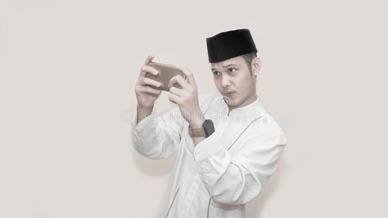 St?ende av den stiliga asiatiska muslim mannen med locket och att anv?nda smartphonen och allvarligt att spela f?r huvud videospe arkivfoto