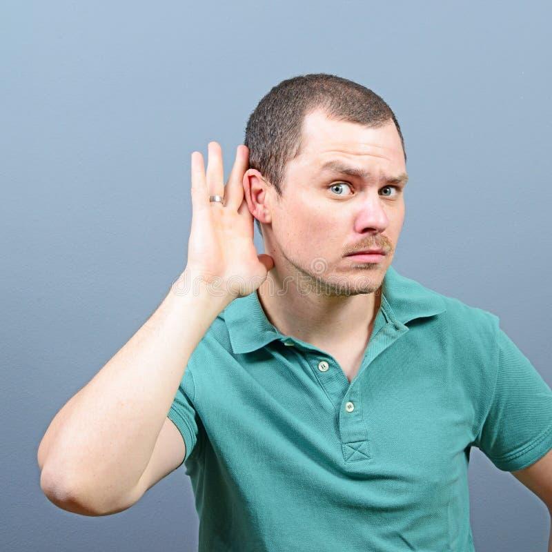 St?ende av den stiliga mannen som lyssnar i hemlighet p? privat konversation arkivfoto