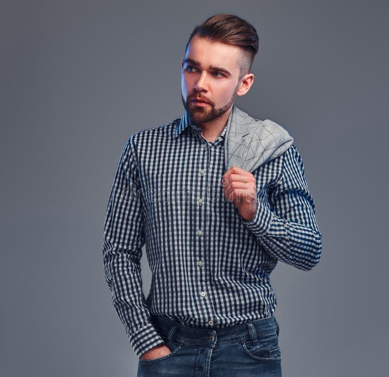 St?ende av den styilish attraktiva mannen i rutig skjorta, grov bomullstvill och blazer p? hans shouder arkivbild
