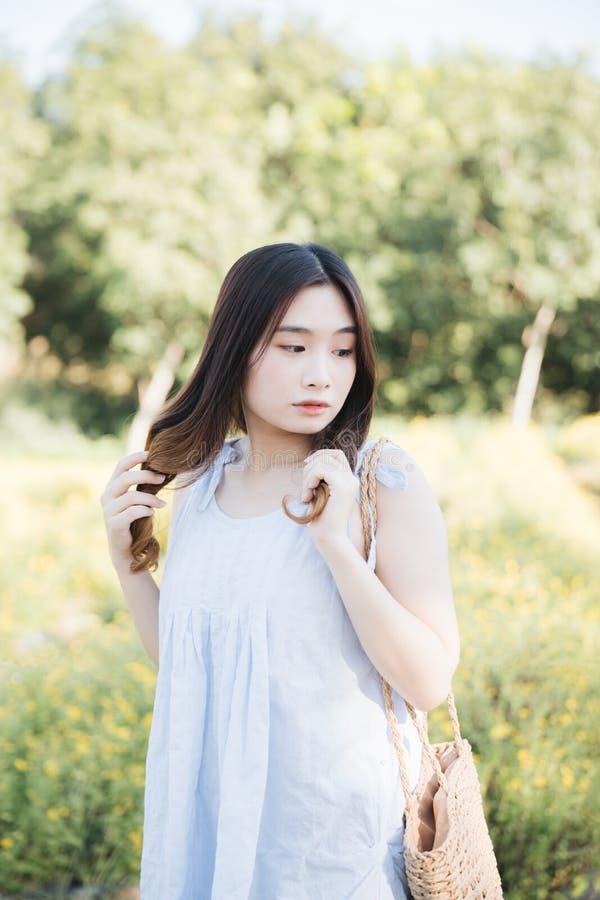 St?ende av den unga asiatiska kvinnaflickan i blommatr?dg?rd royaltyfria foton