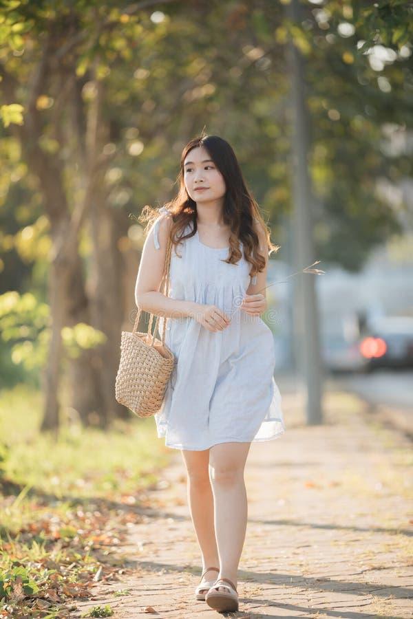 St?ende av den unga asiatiska kvinnaflickan i blommatr?dg?rd arkivfoton