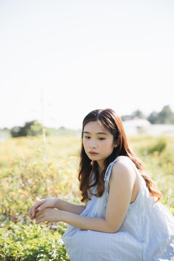 St?ende av den unga asiatiska kvinnaflickan som sitter i blommatr?dg?rd arkivbild