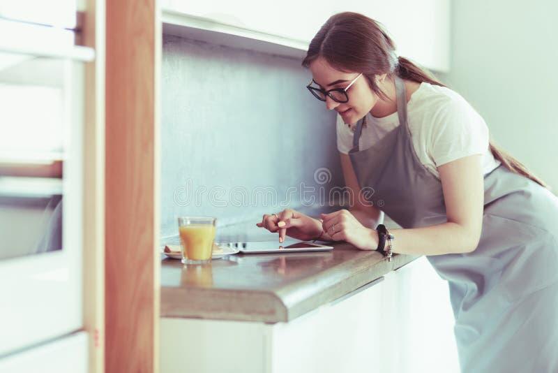 St?ende av den unga attraktiva caucasian brunetthemmafrun p? k?k Morgonen med kuper av kaffe- och tabletPC royaltyfri bild