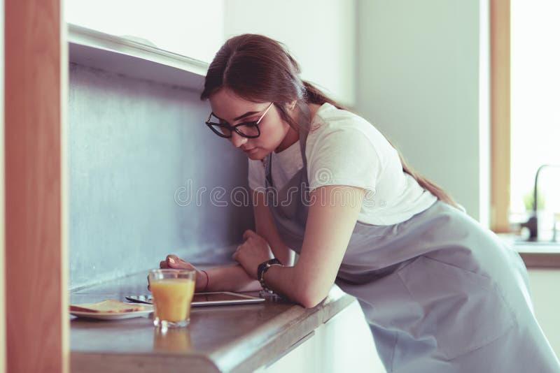 St?ende av den unga attraktiva caucasian brunetthemmafrun p? k?k Morgonen med kuper av kaffe- och tabletPC fotografering för bildbyråer