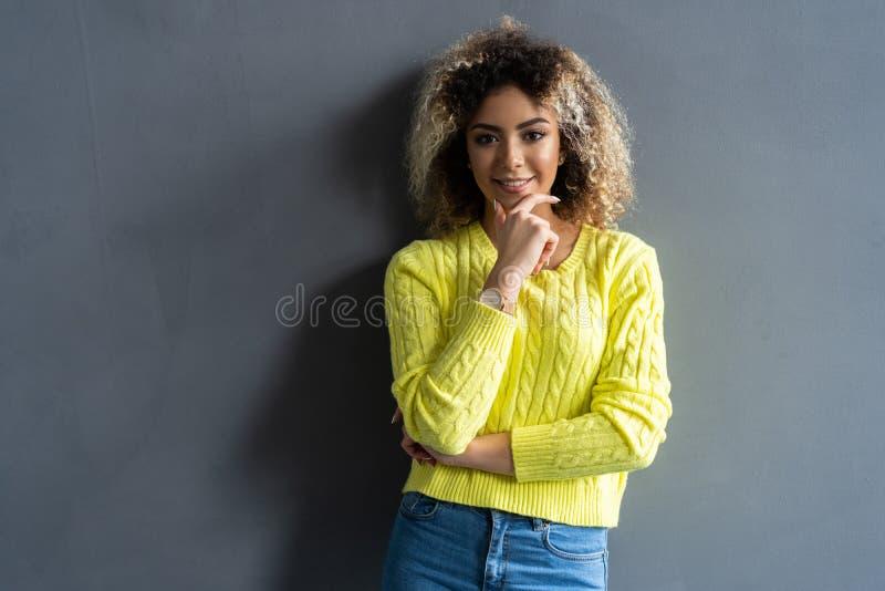 St?ende av den unga h?rliga gulliga gladlynta svarta flickan som ler se kameran ?ver gr? bakgrund fotografering för bildbyråer