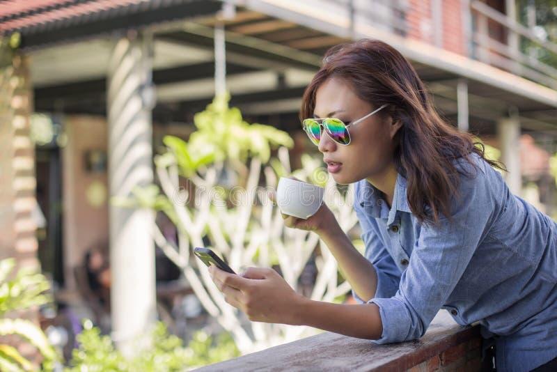 St?ende av den unga hipsterkvinnan som kopplar av p? en balkong p? en solig sommar Att le tycker om med naturen fotografering för bildbyråer