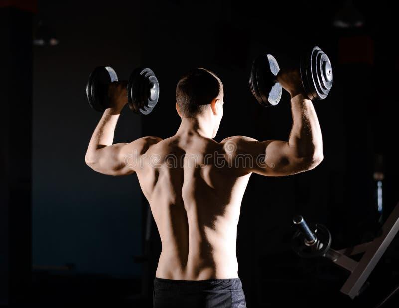 St?ende av den unga idrottsmannen som lyfter tunga hantlar i idrottshall Kondition och sunt livsstilbegrepp dramatisk lighting arkivfoton