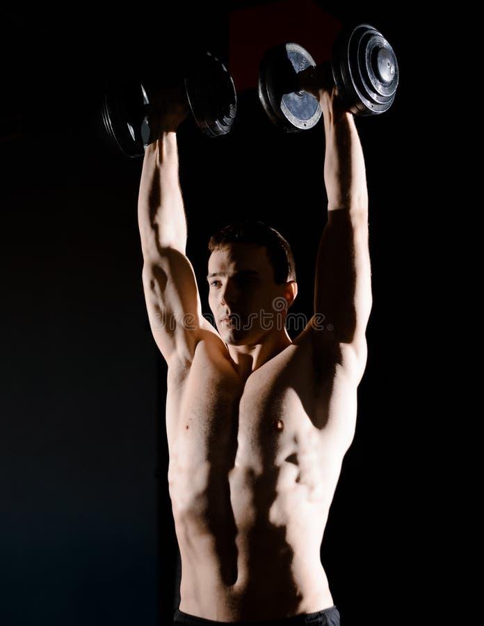 St?ende av den unga idrottsmannen som lyfter tunga hantlar i idrottshall Kondition och sunt livsstilbegrepp dramatisk lighting royaltyfri bild