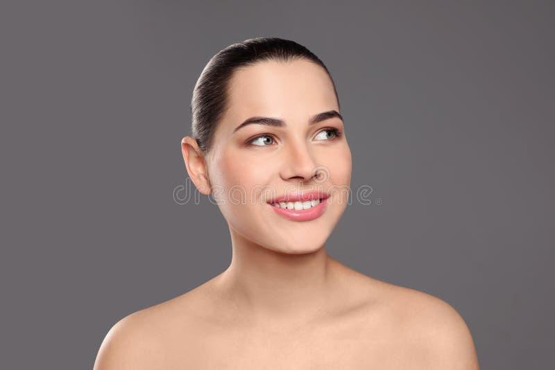 St?ende av den unga kvinnan med den h?rliga framsidan och naturlig makeup arkivbild