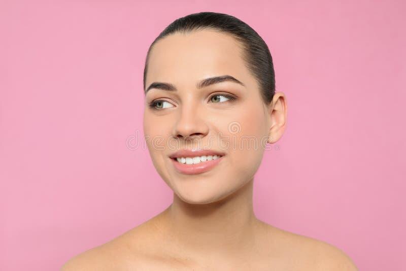 St?ende av den unga kvinnan med den h?rliga framsidan och naturlig makeup arkivfoton