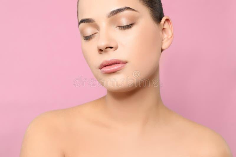 St?ende av den unga kvinnan med den h?rliga framsidan och naturlig makeup p? f?rgbakgrund royaltyfria bilder