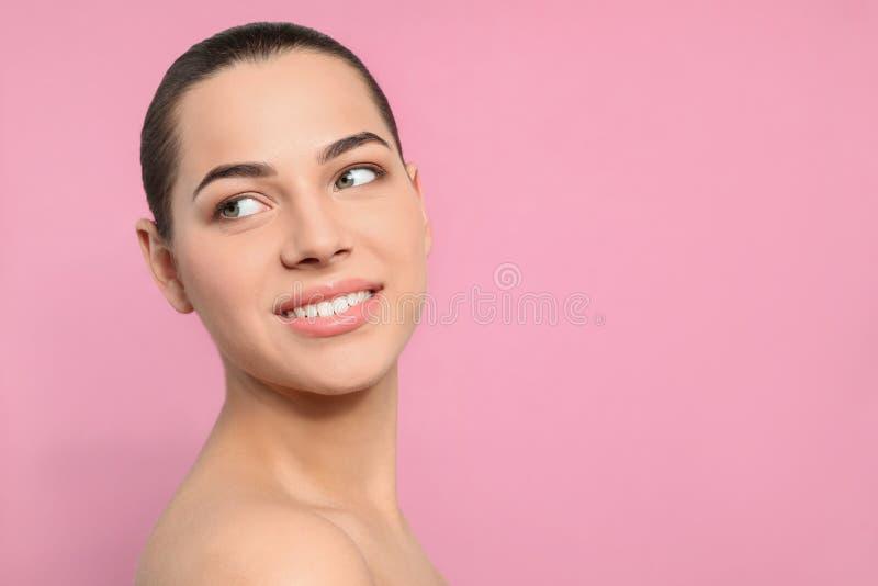 St?ende av den unga kvinnan med den h?rliga framsidan och naturlig makeup p? f?rgbakgrund arkivfoto
