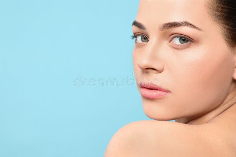 St?ende av den unga kvinnan med den h?rliga framsidan och naturlig makeup p? f?rgbakgrund Utrymme f?r text royaltyfri foto