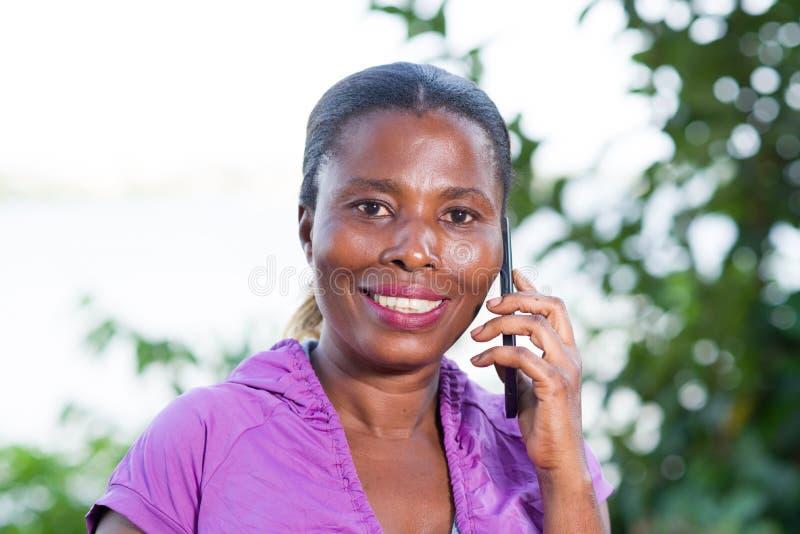 St?ende av den unga kvinnan p? telefonen royaltyfria bilder