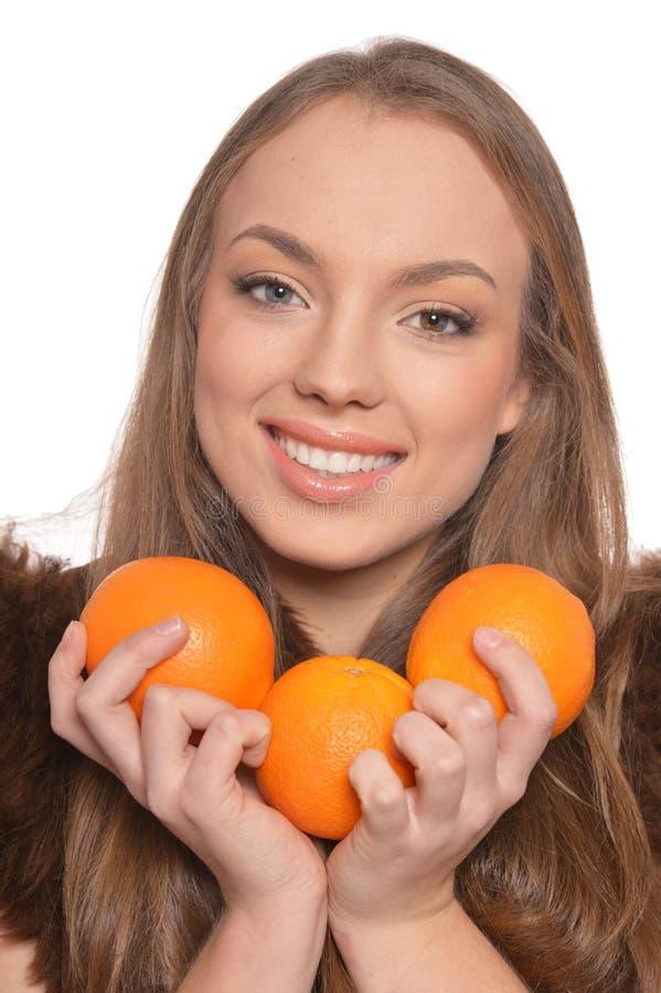 St?ende av den unga kvinnan som poserar med apelsiner p? vit bakgrund royaltyfri fotografi