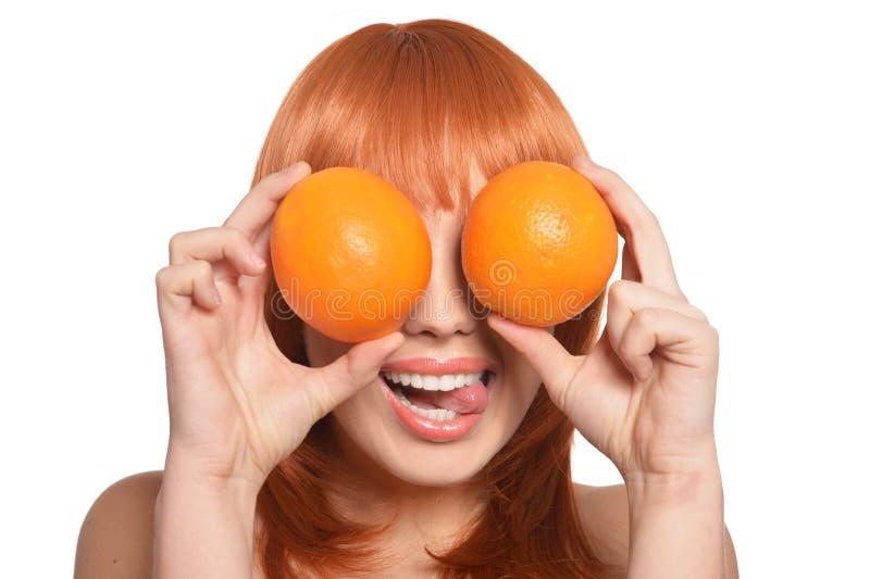 St?ende av den unga kvinnan som poserar med apelsiner p? vit bakgrund royaltyfri foto
