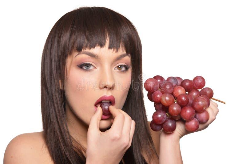 St?ende av den unga kvinnan som poserar med druvor p? vit bakgrund royaltyfri fotografi