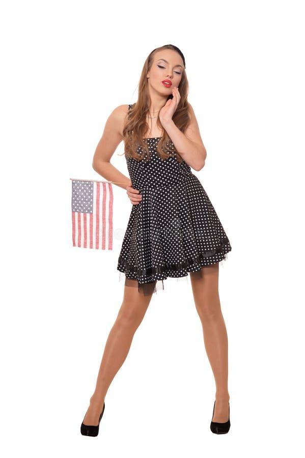 St?ende av den unga kvinnan som poserar med flaggan av USA p? vit bakgrund arkivbilder