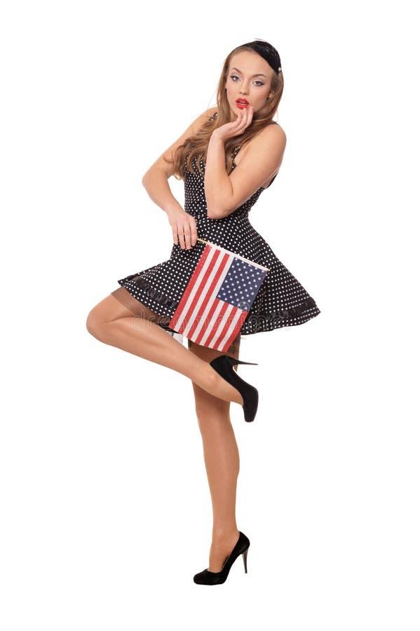 St?ende av den unga kvinnan som poserar med flaggan av USA p? vit bakgrund arkivbild