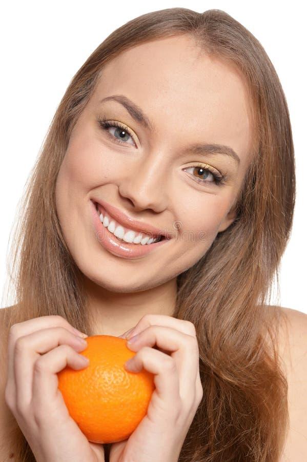 St?ende av den unga kvinnan som poserar med isolerade apelsiner arkivbild