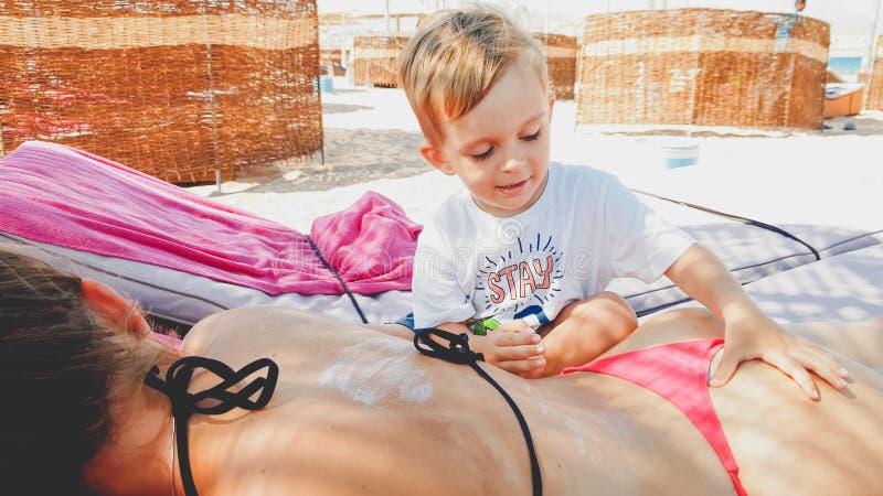 St?ende av den unga modern som ligger p? sunbed p? stranden medan hennes barnson som g?r henne en massage royaltyfri fotografi