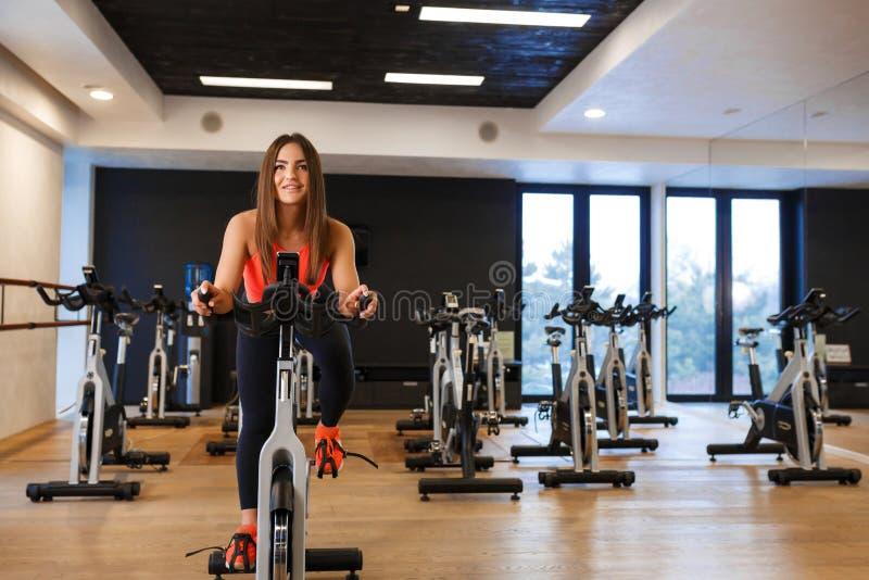 St?ende av den unga slanka kvinnan i sportweargenomk?rare p? motionscykelen i idrottshall Sport- och wellnesslivsstilbegrepp royaltyfri bild
