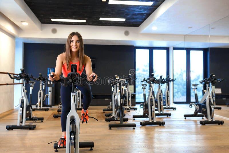 St?ende av den unga slanka kvinnan i sportweargenomk?rare p? motionscykelen i idrottshall Sport- och wellnesslivsstilbegrepp fotografering för bildbyråer