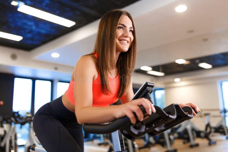 St?ende av den unga slanka kvinnan i sportweargenomk?rare p? motionscykelen i idrottshall Sport- och wellnesslivsstilbegrepp royaltyfria bilder