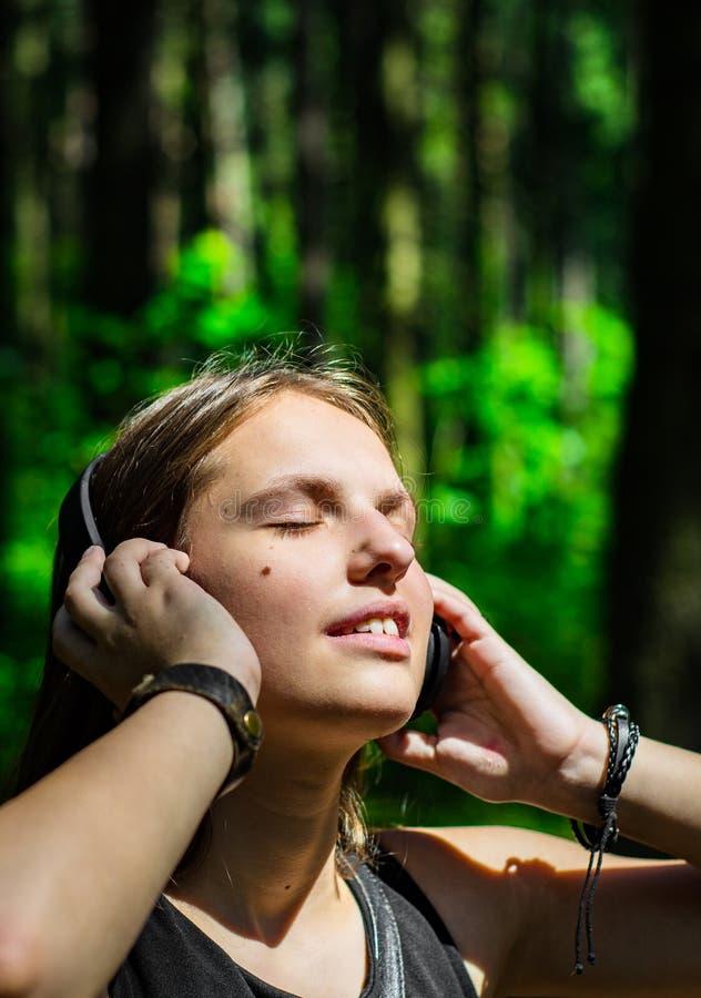 St?ende av den unga ton?ringbrunettflickan med l?ngt h?r Lycklig ung kvinna som lyssnar till musik med hörlurar i skog royaltyfri foto