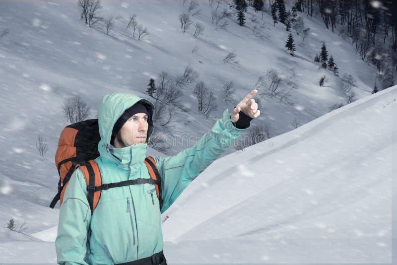 St?ende av den ?ventyrliga unga mannen p? vinterbergssidasikt som ut pekar arkivbilder