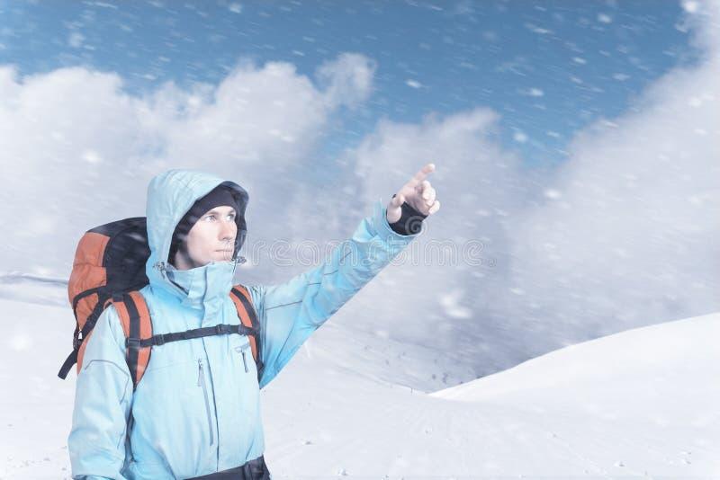 St?ende av den ?ventyrliga unga mannen p? vinterbergssidasikt som ut pekar arkivfoton