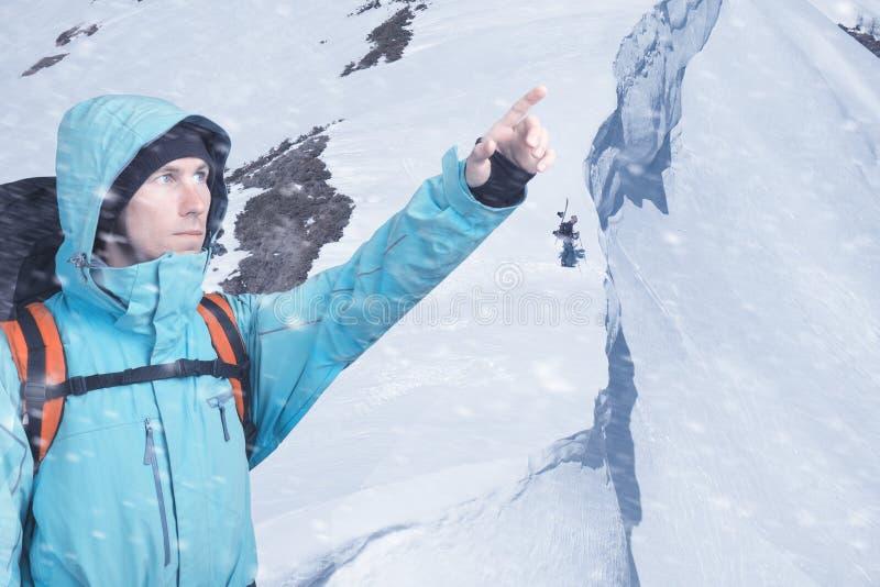 St?ende av den ?ventyrliga unga mannen p? vinterbergssidasikt som ut pekar royaltyfri fotografi