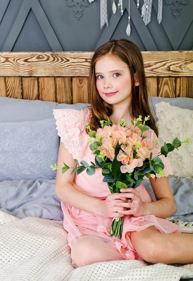 St?ende av det f?rtjusande le liten flickabarnet i prinsessakl?nningen som sitter p? s?ngen royaltyfri bild