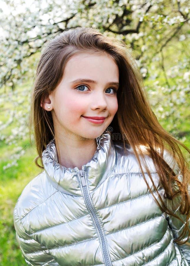 St?ende av det f?rtjusande le liten flickabarnet utomhus i v?rdag royaltyfri bild