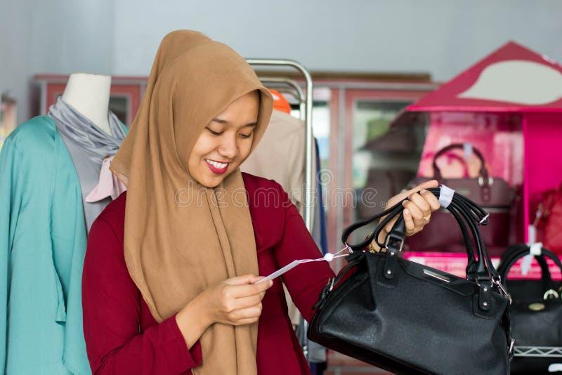 St?ende av det kvinnliga ?gare- och dr?ktanseendet f?r asiatisk hijab med den svarta handv?skan i hennes boutiquemodelager, ungt  arkivbilder