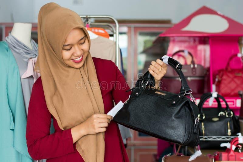 St?ende av det kvinnliga ?gare- och dr?ktanseendet f?r asiatisk hijab med den svarta handv?skan i hennes boutiquemodelager, ungt  arkivbild