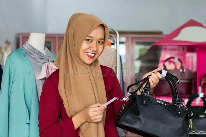 St?ende av det kvinnliga ?gare- och dr?ktanseendet f?r asiatisk hijab med den svarta handv?skan i hennes boutiquemodelager, ungt  royaltyfri bild